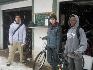 Mechanics and mentors Sergio and Karen watch the snow fall with Mawuli. We stayed open even through April's snow!