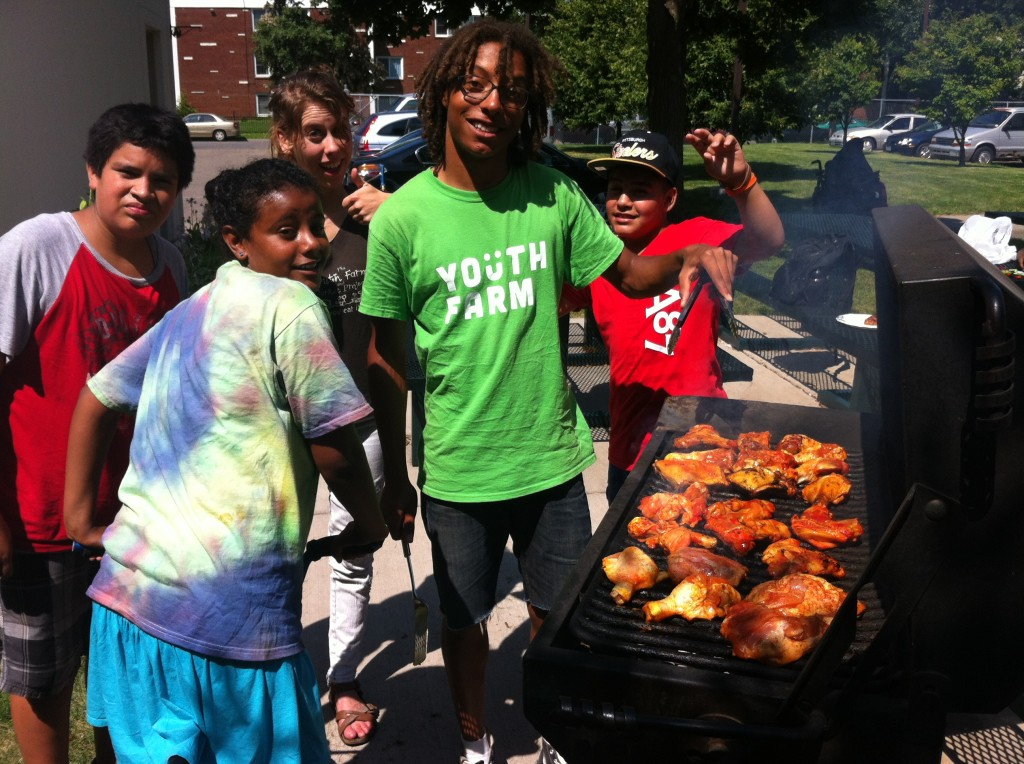 Nazeem and a crew grilling chicken marinated by a Youth Farm mom