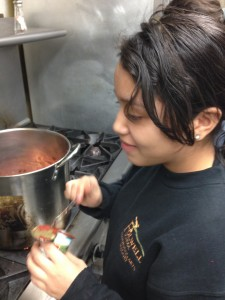 Dulce cooking up sauce with Lyndale tomatoes