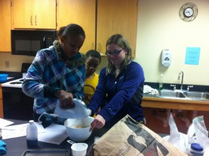 A volunteer from St Kate's works together with a Youth Farmer to make frosting.