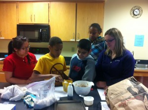 Volunteers work with Youth Farmers to read a recipe.